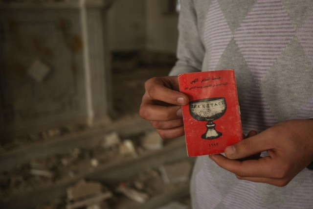 A man displays a small liturgical book in early November inside a destroyed Orthodox church near Damascus, Syria. (CNS/EPA)