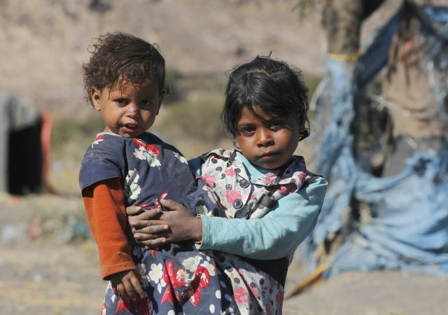 A girl holds her sister near a  makeshift shelter at a camp for displaced people on the outskirts of Sana'a, Yemen. (CNS/EPA)
