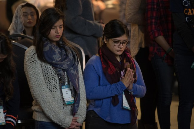 Young adults pray during a Mass during the Jan. 3-7 biennial SEEK conference in San Antonio. (CNS/courtesy FOCUS)