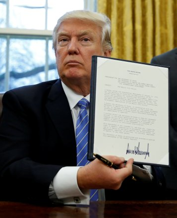 """President Donald J. Trump holds up his executive order reinstating the """"Mexico City Policy"""" banning federal funding of abortion-providing groups abroad after he signed it Jan. 23 in the Oval Office of the White House in Washington. (CNS/Reuters)"""