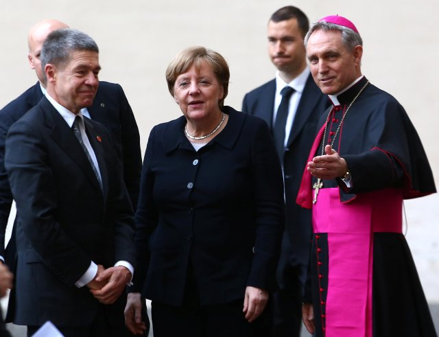 German Chancellor Angela Merkel and her husband, Joachim Sauer, are greeted by Archbishop Georg Ganswein, prefect of the papal household, right, as they arrive March 24 for the European Union summit with Pope Francis at the Vatican. (CNS/Reuters)
