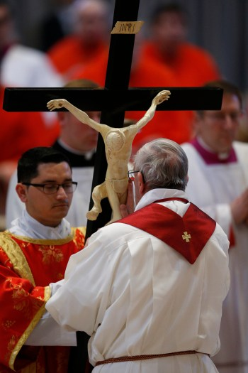 Pope Francis venerates the crucifix as he leads the Good Friday service in St. Peter's Basilica at the Vatican April 14. (CNS/Paul Haring)