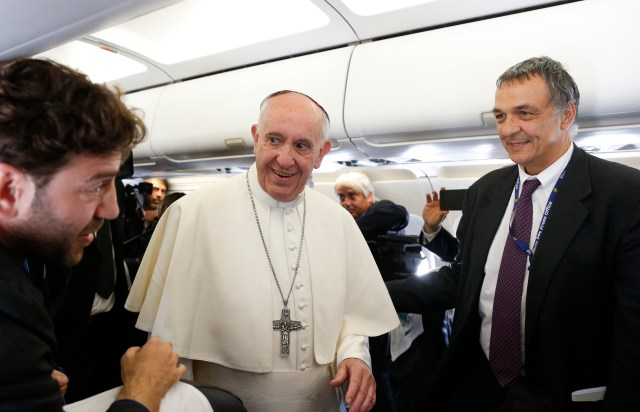 Pope Francis greets journalists Carmelo Camilli of Reuters and Maurizio Brambatti of ANSA aboard his flight from Rome to Portugal May 12. The pope was making a two-day visit to Fatima to commemorate the 100th anniversary of the Marian apparitions and to canonize Sts. Francisco and Jacinta Marto, two of the three seers. (CNS/Paul Haring)