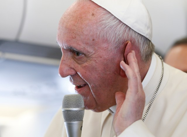 Pope Francis listens to a question as he speaks with journalists aboard his flight from Portugal to Rome May 13. The pope made a two-day visit to Fatima to commemorate the 100th anniversary of the Marian apparitions and to canonize Sts. Francisco and Jacinta Marto, two of the young seers. (CNS/Paul Haring)