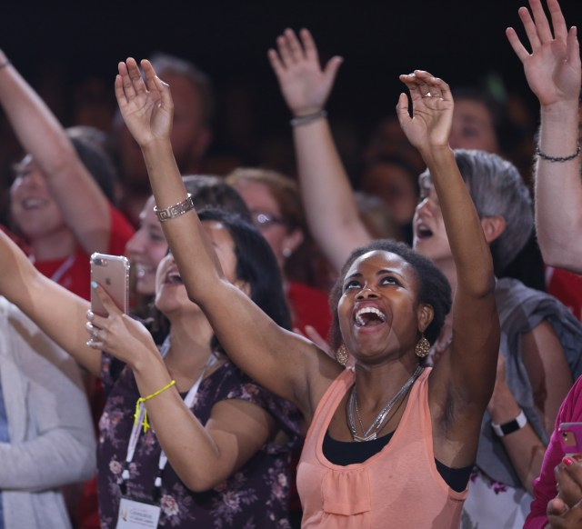 "Young people lift their arms in prayer as Catholic musician Matt Maher performs July 3 during the ""Convocation of Catholic Leaders: The Joy of the Gospel in America"" in Orlando, Fla. Leaders from dioceses and various Catholic organizations gathered for the July 1-4 convocation. (CNS/Bob Roller)"