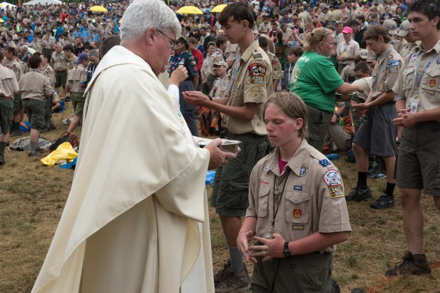 A Scout receives Communion during Mass July 23 at the Boy Scout Jamboree in Glen Jean, W.Va. (CNS/courtesy Boy Scouts of America)