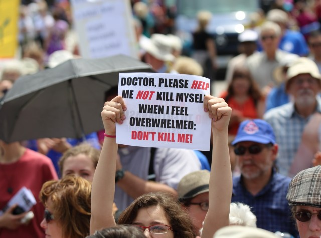 A woman holds up a sign during a rally against assisted suicide in 2016 on Parliament Hill in Ottawa, Ontario. (CNS/Art Babych)