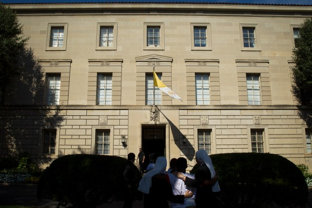 People are seen outside the Vatican Embassy, or apostolic nunciature, in Washington in 2014. A member of the Vatican diplomatic corps serving in Washington has been recalled to the Vatican where he is involved in a criminal investigation involving child pornography, the Vatican said. (CNS/Tyler Orburn)
