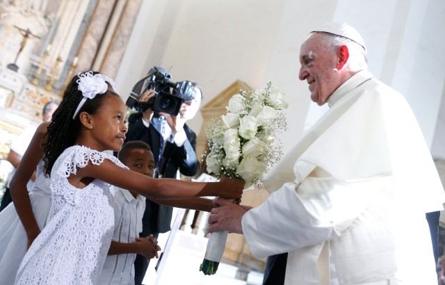 Pope Francis accepts flowers from a girl as he arrives to visit the Shrine of St. Peter Claver in Cartagena, Colombia, Sept. 10. (CNS/Paul Haring)