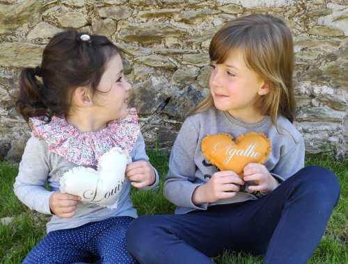 deux petites filles assises avec leur coussin cœur personnalisé dans les mains