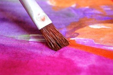 Kreativität entfesseln - wie geht das? Nahaufnahme Pinsel gleitet über Papier mit Farben