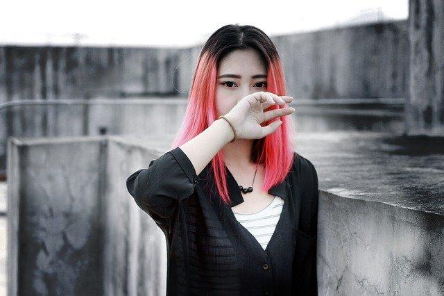 Gender Data Gap: junge Frau mit roten Haaren bedeckt nachdenklich mit den Mund