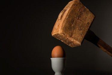Ratschläge: großer Holzhammer zerschlägt kleines Ei