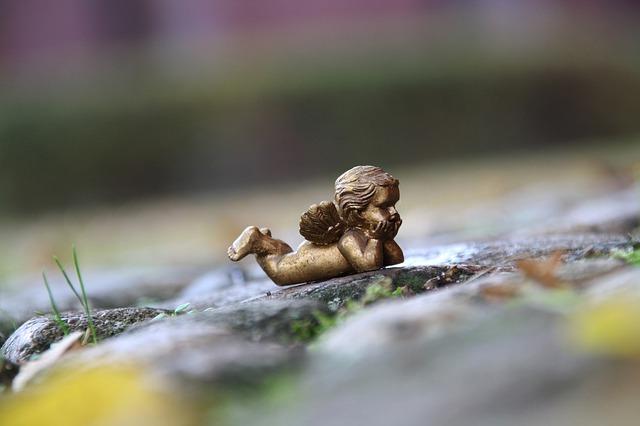 Mitfühlend leben: Skulptur: golder nachdenklicher Engel auf Stein bei Regen