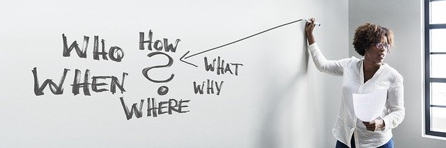 Kommunikationssperre Gordon: Fragen - Dozentin zeigt mit Stab auf Whiteboard mit vielen Fragen