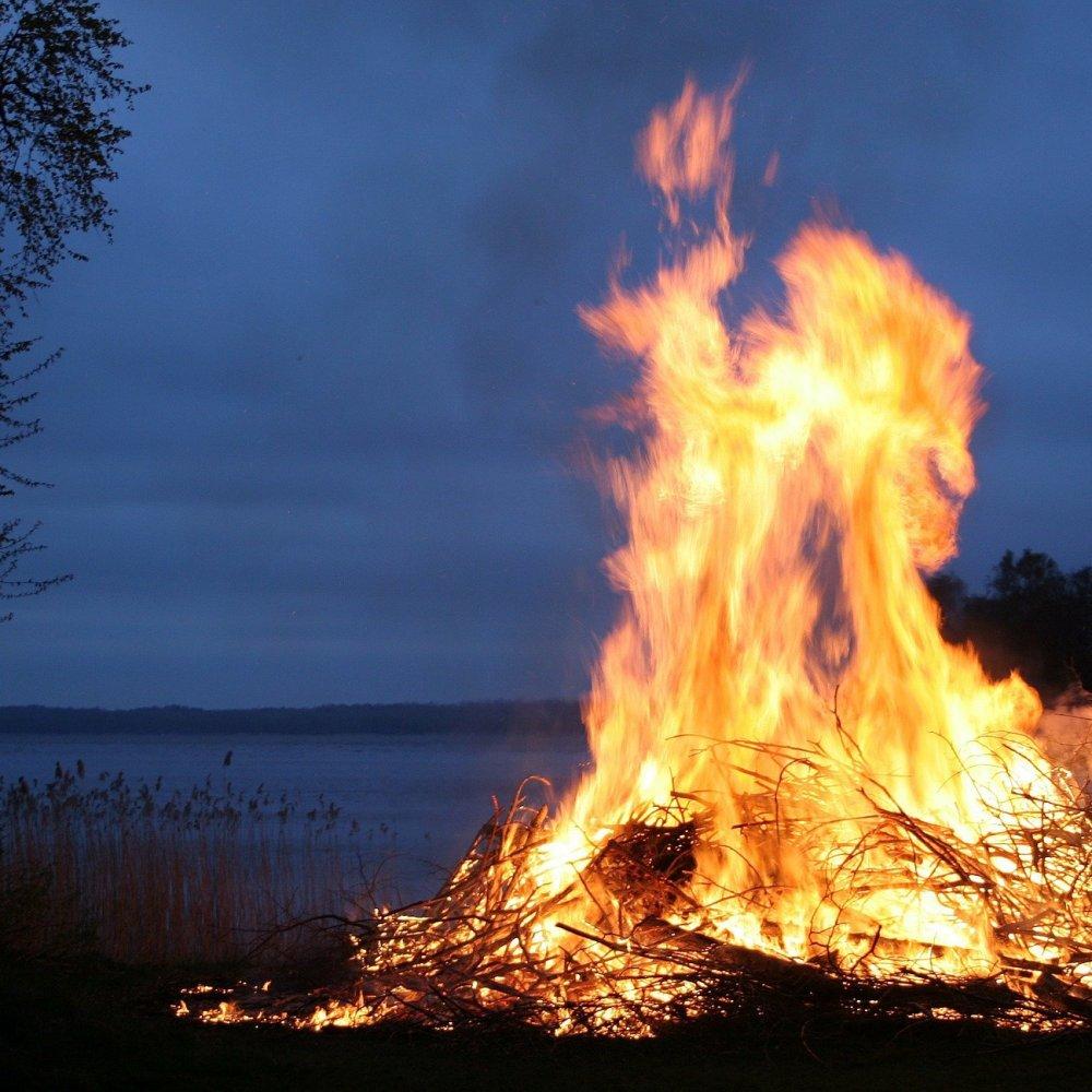 Feuer lodert in der Abenddämmerung vor einem See