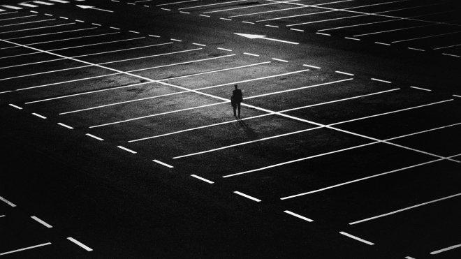 ein Mann allein im Regen auf Parkplatz-wirkt einsam und traurig