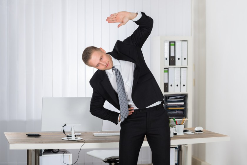 Businessman Stretching In Office