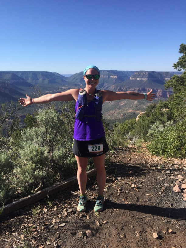 Girl standing in front of the Grand Canyon wearing a purple tank top, black skirt and a running vest.