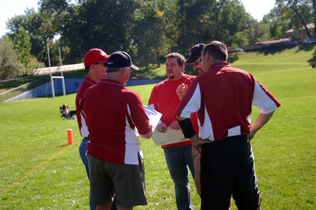 coaching youth football coaches talking on sideline