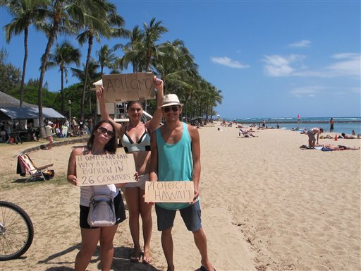 Pohai George, left, Ashley Montogmery and Nathaniel Whittaker, right, protested against Monsanto at a Waikiki Beach rally in Honolulu on Saturday, May 23, 2015. They were part of an international day of protests against the company. (AP Photo/Cathy Bussewitz)