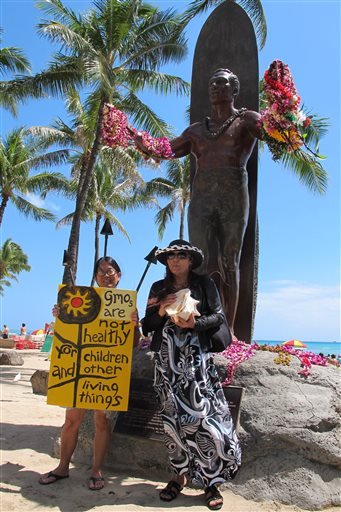 Karen Murray, left, and Diane Marshall, right, both teachers from Honolulu, protested against Monsanto at a Waikiki Beach rally in Honolulu on Saturday, May 23, 2015. They were part of an international day of protests against the company. (AP Photo/Cathy Bussewitz)