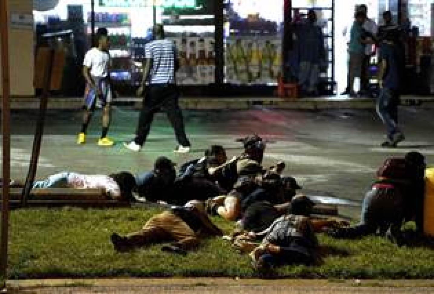 Image: Protesters fall to the ground to take cover after shots were fired in Ferguson, Missour