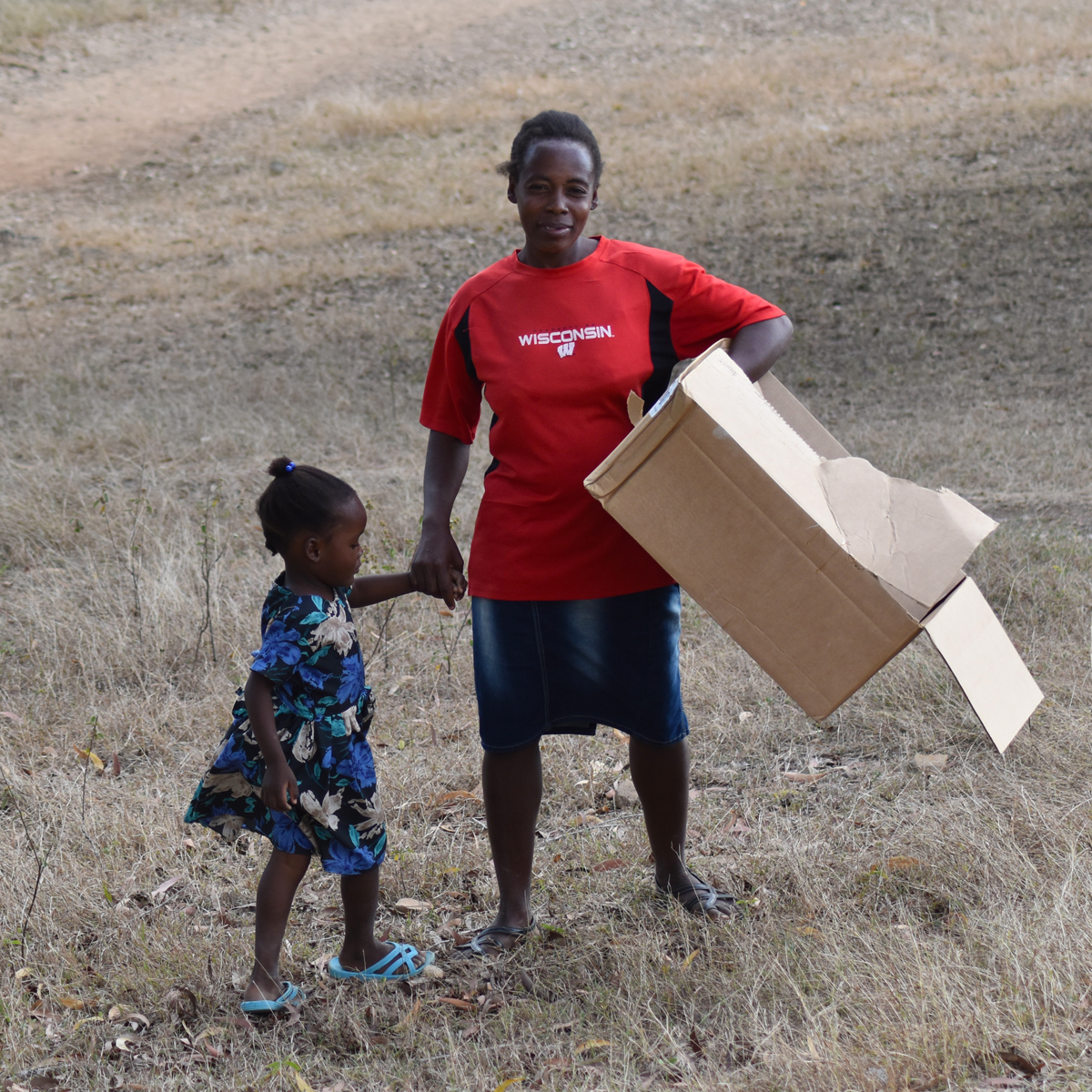 woman holding cardboard with child
