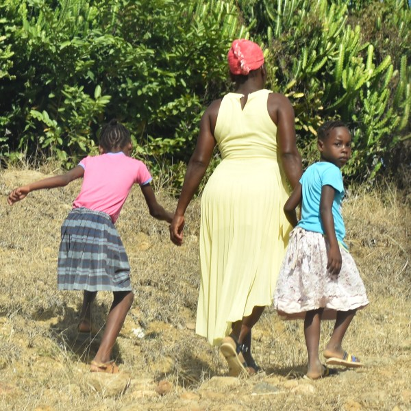 mother and two children walking along road