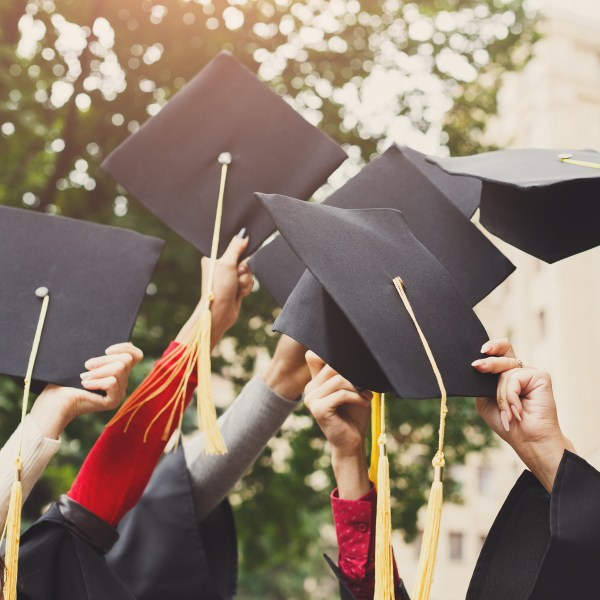 group of graduates throwing graduation caps in the air