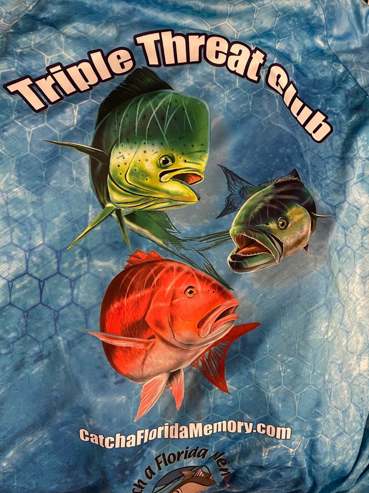 Blue honeycomb Triple Threat Club shirt with a Mahi Mahi, Red Snapper, and Bluefish on it. catchafloridamemory.com and logo on the bottom