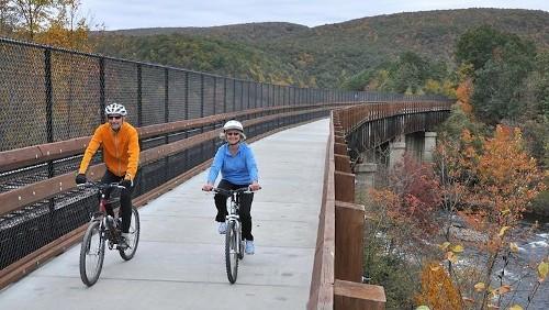 tow bicyclists on a multimodal rail bridge with bike trail
