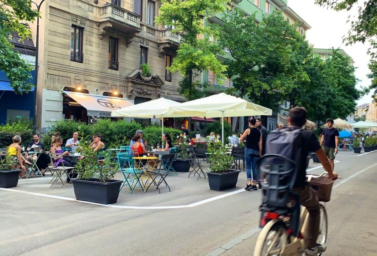Photo shows restaurant tables set up in the street, with flower planters surrounding them.