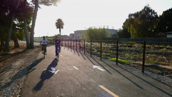 Two cyclists on a paved separated bike path next to railroad tracks.