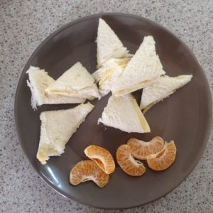 A plate of orange segments and sandwiches