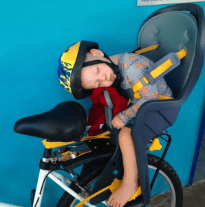 A baby asleep in a bike seat
