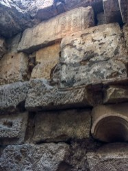 Ancient City wall, built from stones, old building materials like the arch in the bottom corner and even a tombstone (top center). Museu d'Història de la Ciutat de Barcelona. Dawn Page / CoastsideSlacking
