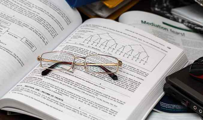 Image: eyeglasses folded in open book, signifying business entities