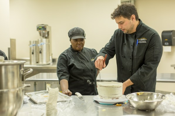 Aaron Russell, instructor and award-winning pastry chef, teaches Baking and Pastry Apprenticeship student Islande Cadely how to apply icing on a layered cake.