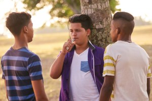 Teenagers smoking electronic cigarette in park.
