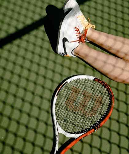 person s feet wearing white and black nike low top sneakers beside lack white and orange wilsons tennis racket