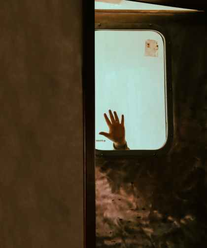person waving hand at window of old train