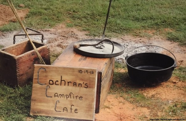 """Dutch oven with a square wood sign that reads """"Cochran's Campfire Cafe"""""""