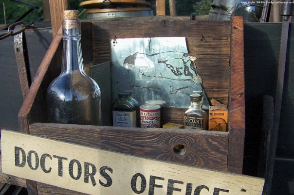 The chuck wagon version of a doctor's office: a wood box hanging on the side board with some bottles and cans.