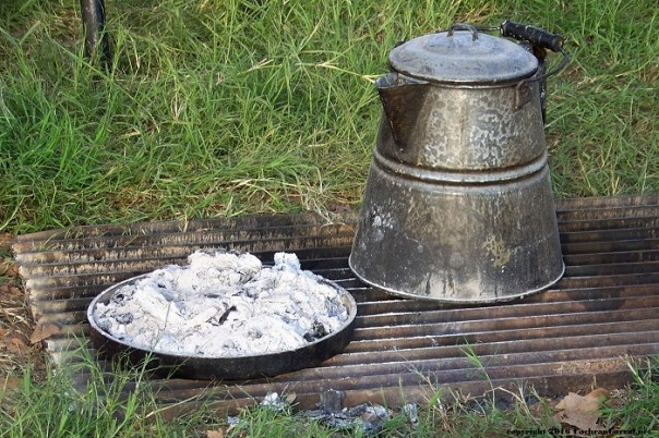 Cowboy coffee pot next to a dutch oven lid with coals on top.