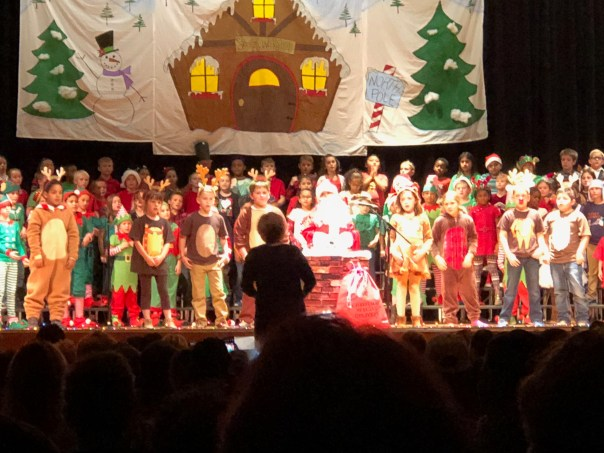 kids singing Christmas at the local school auditorium