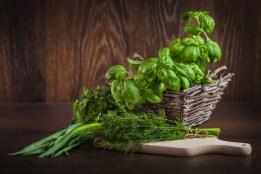 Fresh organic green herbs on wood