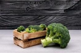 bunches of broccoli in wooden box near the whole fresh broccoli