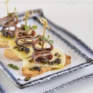 Tapenade en pintxo de queso manchego, anchoas y alcaparras fritas