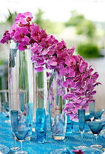 Trailing centerpiece of purple phalaenopsis orchids on top of cylinders with blue glasses